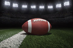 Collegeartfußball auf Feld mit Streifen unter Stadion beleuchtet Lizenzfreie Stockbilder