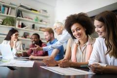 Colleghe allegri in ufficio nel corso della riunione della societ? fotografie stock