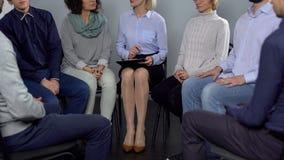 Colleghe che si siedono nel cerchio alla sessione di team-building, analisi di comportamento, consiglio immagini stock