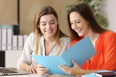 Colleghe felici che leggono un rapporto Fotografia Stock