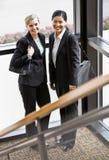 Colleghe femminili che propongono insieme nell'angolo Fotografia Stock