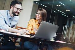Colleghe moderni che discutono durante il processo di lavoro nell'ufficio del sottotetto Giovane squadra di affari che lavora con Immagini Stock