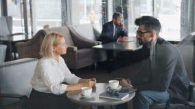 Colleghe uomo e donna che parlano in caffè durante gesturing di conversazione dell'intervallo di pranzo video d archivio