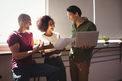 Colleghi allegri di affari che lavorano insieme dalla finestra all'ufficio Fotografia Stock