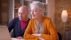 Colleghi caucasici dai capelli grigi senior che parlano di di progetto di lavoro futuro con il computer portatile in ufficio archivi video