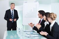 Colleghi che applaudono dopo una presentazione del personale Immagine Stock Libera da Diritti