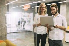 Colleghi che confrontano le idee nell'ufficio Immagine Stock