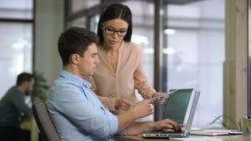 Colleghi che digitano i dati dai grafici nel computer per controllare crescita e declino stock footage