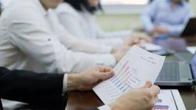 Colleghi che discutono i dati nella riunione d'affari, dividente i grafici di statistica, gruppo video d archivio