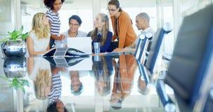 Colleghi che discutono sopra il computer portatile alla tavola 4k archivi video