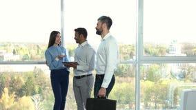 Colleghi che flirtano sul lavoro, gente occupata che cammina da parte a parte stock footage