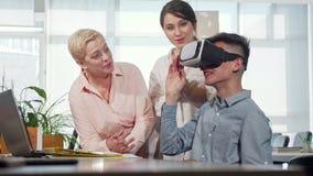 Colleghi che guardano giovane uomo d'affari usando i vetri del vr 3d stock footage