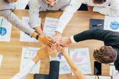Colleghi che impilano le mani sopra la tavola con le carte fotografie stock libere da diritti