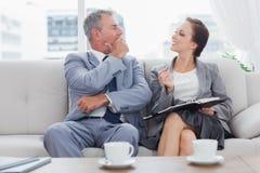 Colleghi che lavorano insieme seduta sul sofà che mangia caffè Immagine Stock