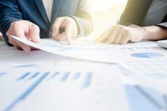 Colleghi del gruppo due di affari che discutono i dati finanziari del grafico sopra fotografia stock libera da diritti