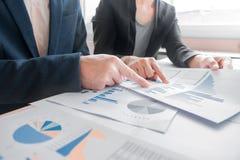 Colleghi del gruppo due di affari che discutono il grafico finanziario di nuovo piano fotografia stock libera da diritti