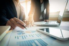 Colleghi del gruppo due di affari che discutono il grafico finanziario di nuovo piano fotografie stock libere da diritti