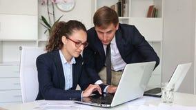 Colleghi della donna che si siedono con i computer portatili sullo scrittorio in ufficio archivi video