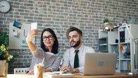 Colleghi della donna e dell'uomo che prendono selfie con la macchina fotografica dello smartphone in ufficio stock footage