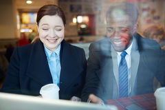 Colleghi di affari che ridono esaminando lo schermo del computer portatile fotografie stock libere da diritti