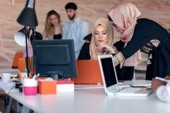 Colleghi di affari nei hijabs che esaminano il monitor del computer fotografia stock