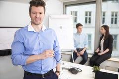 Colleghi di Holding Eyeglasses While dell'uomo d'affari che si siedono su Windo immagine stock