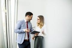 Colleghi felici di affari in ufficio moderno facendo uso della compressa Immagine Stock