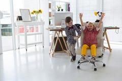 Colleghi maschii allegri che spingono donna di affari che si siede sulla sedia in ufficio Fotografie Stock Libere da Diritti