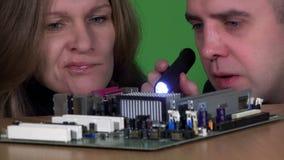 Colleghi maschii e femminili del tecnico che esaminano il consiglio principale del computer difettoso video d archivio