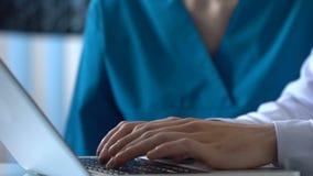 Colleghi medici che cercano informazioni di malattia sul computer portatile online, ricerca video d archivio