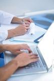 Colleghi medici che lavorano con il computer portatile e che prendono le note Fotografie Stock Libere da Diritti