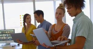 colleghi Multi-etnici di affari che discutono e che lavorano sopra il computer portatile e la compressa digitale in moderno fuori archivi video