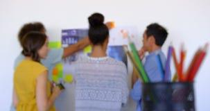 colleghi Multi-etnici di affari che discutono sopra i grafici e le note appiccicose nell'ufficio moderno 4k stock footage