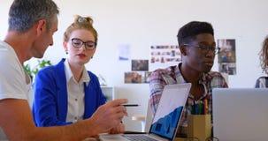 colleghi Multi-etnici di affari che discutono sopra il computer portatile nell'ufficio moderno 4 4k archivi video