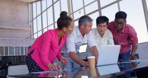 colleghi Multi-etnici di affari che discutono sopra il computer portatile in una riunione all'ufficio moderno 4k archivi video