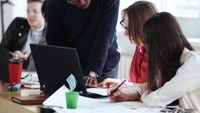 Colleghi multietnici intelligenti felici, giovane e due donne, lavoro insieme ai documenti all'ufficio moderno sano stock footage