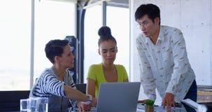 colleghi Muti-etnici di affari che discutono sopra il computer portatile in una riunione all'ufficio moderno 4k archivi video