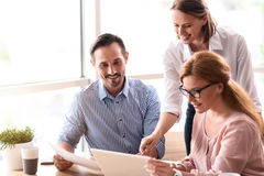 Colleghi positivi che discutono progetto Immagine Stock