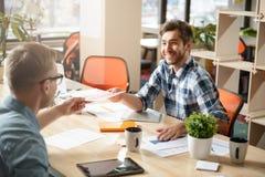 Colleghi positivi che si siedono alla tavola Fotografia Stock