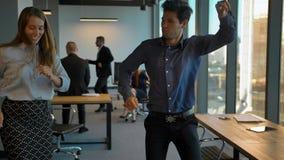 Colleghi sicuri attraenti che celebrano con il ballo nel loro ufficio archivi video