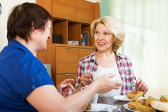 Colleghi sorridenti che bevono tè e che chiacchierano durante la pausa caffè Fotografia Stock Libera da Diritti