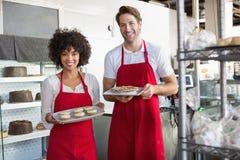colleghi sorridenti che mostrano piatto del deserto Immagini Stock
