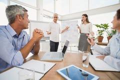 Colleghi sorridenti di affari che conducono presentazione Fotografia Stock Libera da Diritti