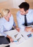 Colleghi sorridenti di affari che discutono le statistiche Immagini Stock Libere da Diritti