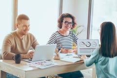 Colleghi sorridenti positivi che lavorano alla tavola fotografie stock libere da diritti
