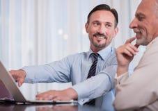 Colleghi sorridenti positivi che si siedono alla tavola Fotografia Stock