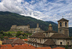 Collegiate Church and Castelgrande castle in Bellinzona, Ticino, Switzerland. View of Collegiate Church and Castelgrande castle with green mountains and Stock Image