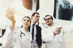 Collegium av doktorer visar röntgenstrålar av ben till affärsmannen som behandlas Bäcken- benröntgenstråle arkivbild
