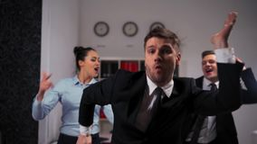 Collegues dancing cheerfully in office in front of the camera. stock footage
