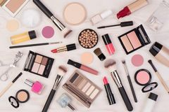 Makeup cosmetics such as eyeshadows, lipstick, mascara and makeup accessories on white, wooden background, top view royalty free stock photography